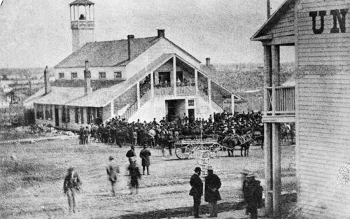 Black and white photograph of a crowd gathered in front of a large white wooden building, quite imposing for the period. The second floor has a balcony accessible via external staircases.