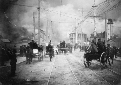 Black and white photograph of a large crowd in a street threatened by smoke. Some people are in buggies with their possessions. Firefighters arrive in wagons.