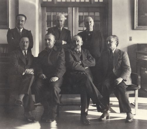Black and white photograph showing seven older men in an exhibition hall. Four sit on a bench, while three stand behind them.  They are all dressed in suits and look serious.