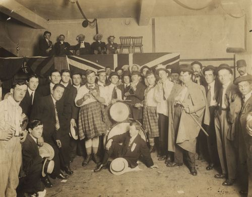 Sepia photography of a group of around thirty men, standing in a semicircle, posing for the camera. They wear suits and ties, except for two who wear kilts. In the centre, a man sits on the floor in front of a drum set. Behind the group, five men sit on a platform draped with a British flag.