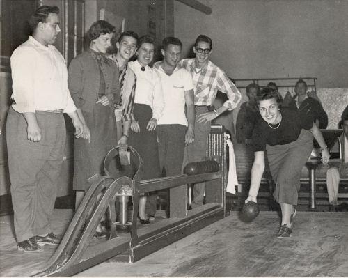 Photographie en noir et blanc de jeunes gens, regroupés autour d'une allée de quilles. Une jeune femme est à faire le lancer de sa boule. Ils s'amusent.