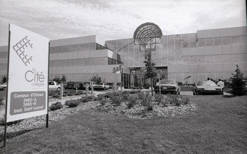 Photographie en noir et blanc d'un édifice d'une grande superficie. Ses trois étages ont de nombreuses fenêtres. Le toit dispose d'un puits de lumière. Quelques voitures sont garées de chaque côté d'une large entrée. Un grand panneau arborant l'enseigne de la Cité collégiale est placé à l'avant de l'édifice.