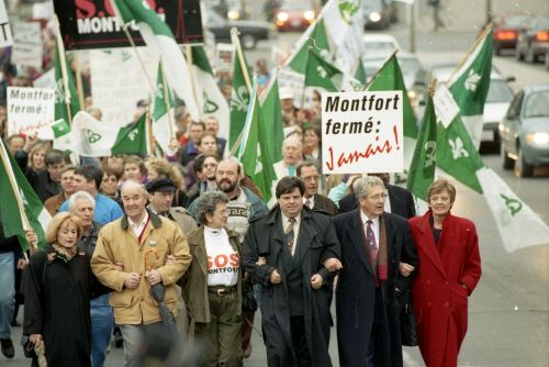 """Colour photograph of a large crowd walking down a city street, demonstrating. They are carrying Franco-Ontarian flags and placards that read, """"Montfort fermé : Jamais !"""" with the """"Jamais"""" positioned obliquely, in stylized red letters. The six people at the front of the crowd – three men and three women, most of them older – walk with their arms linked."""
