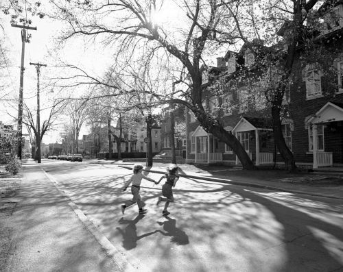 Black and white photograph of two children crossing a residential street, hand in hand. On both sides of the street, brick row houses and large trees.
