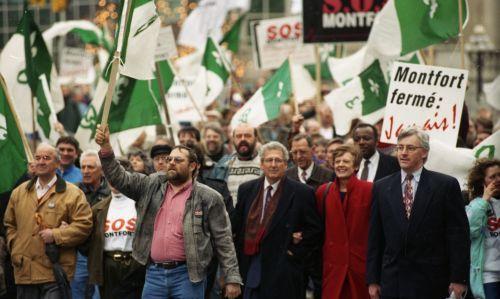 Photographie en couleur d'une manifestation, en pleine rue. Un manifestant porte une pancarte qui se lit : «Montfort fermé : Jamais ! ». La foule agite des drapeaux franco-ontariens.