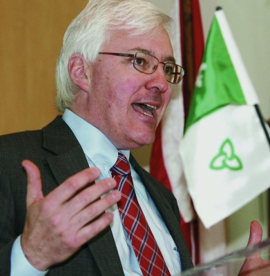 Colour photograph of a mature man with white hair and glasses, in a dark gray suit, white shirt, and red-patterned tie. He is standing in front of a Franco-Ontarian flag, delivering a speech.