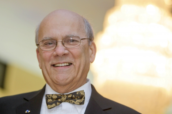 Close-up colour photograph of an older, balding man wearing glasses, smiling at the camera. He wears a dark gray suit, white shirt and gray-gold bow tie.