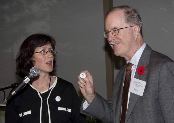 Colour photograph of two people standing in front of a microphone: a middle-aged, dark-haired women wearing a dark suit with white trim, and an older man wearing a gray suit, white shirt and brown tie. Both wear glasses. The man is holding a pin, which he is presenting to the woman.