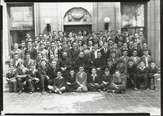 Black and white photograph of about eighty young boy, in front of a stone building. The boys in the first row are kneeling, in the next two rows sitting, and in the other five rows standing. All boys wear suits, with some also wearing ties. Three priests in cassocks are seated at the center of the group.