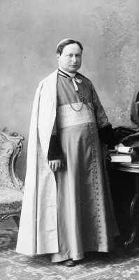 Black and white photograph of a mature man wearing the liturgical garments of an archbishop. His short brown hair is hidden under his skullcap. He stands next to a table, a document in his left hand. He suffers from a slight strabismus.
