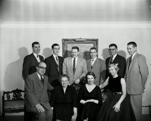 Black and white family photograph. Standing in the back, two middle-aged men and four young men. Sitting in front, an older man and woman, and two young women. The men all wear suits; the women wear black dresses.
