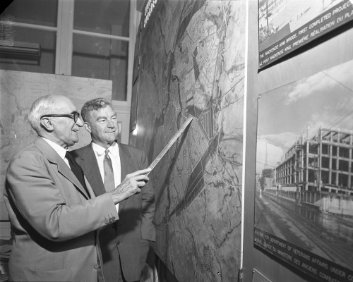 Black and white photograph of an older man and a middle-aged man, both wearing suits and ties. The two men are smiling as they look at a large, very detailed aerial map hanging on the wall. The older man is using a ruler to indicate a specific location on the map.