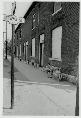 Black and white photograph of a young boy pushing a preschooler in a stroller alongside a brick building. A road sign indicates that they are at an Ottawa Street intersection.