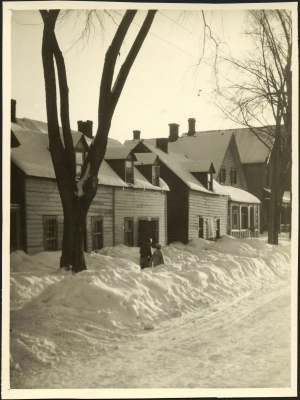 Black and white photograph of a residential street in winter, with wooden two-storey houses in need of maintenance. A couple walks along the snowy sidewalk.