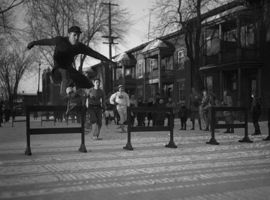 Black and white photograph of three young men participating in a snowshoe hurdle race in an urban park. In the foreground, a young man jumping a hurdle. Spectators watch the race.