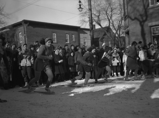 Black and white photograph of three young women and a middle-aged woman participating in a snowshoe race in the city, against a backdrop of houses. A crowd watches the race.