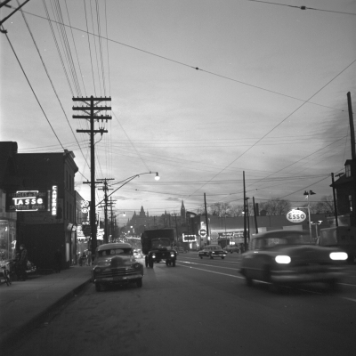 Black and white photograph of a boulevard at night. Car headlights and shop signs illuminate the photograph.