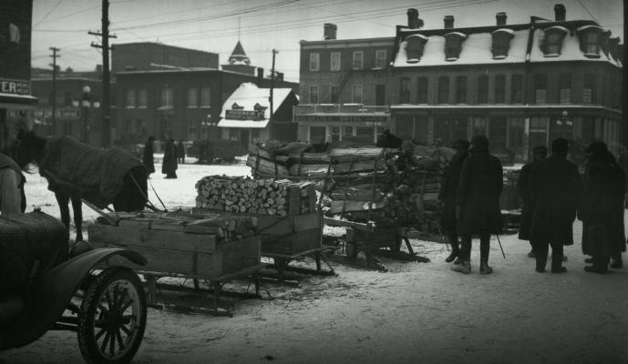 Black-white photograph of a marketplace in winter. In the foreground, horse-drawn sleds laden with wood. Several men, dressed in coats and hats, stand beside the sleds.