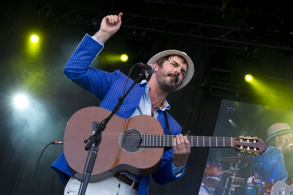 Colour photograph of a mature man on stage. He has a short, black beard, and he wears a hat, royal blue jacket, and white pants. He plays the acoustic guitar and sings in front of a microphone. The photograph is taken at a low angle, and the image is reflected on a surface to his left.