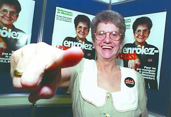 """Colour photograph of a mature woman, smiling and mimicking the gesture she herself is making on the posters behind her. On the poster she wears an S.O.S. Montfort button and points her finger at the camera. Superimposed on her chest, the slogan: """"Enrôlez-vous !'"""