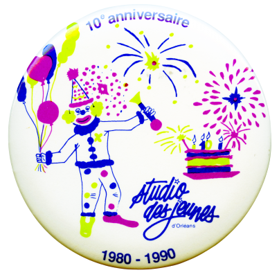 Photographie d'un macaron sur lequel figurent, sur fond blanc, un clown tenant des ballons, un gateau d'anniversaire et un feu d'artifice en bleu, vert clair et fuhsia. Le nom de l'organisme apparaît en bleu, ainsi que la mention de l'anniversaire.