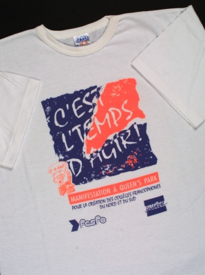 "Photograph of a white T-shirt with the words, in blue and bright orange: ""C'est l'temps d'agir !"" (It's time to act!). The purpose of the demonstration and the logos of two organizations are also printed on the T-shirt."