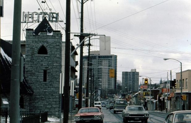 Photographie en couleur d'une rue passante où circulent de nombreuses voitures. La rue est bordée de commerces. Au loin, on remarque de grands édifices.