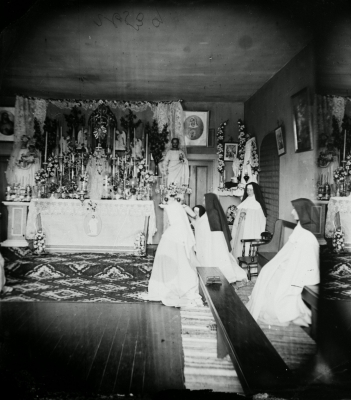 Black and white photograph of a novice and four nuns praying in a modest chapel. The altar is decorated with candlesticks, flowers, statues and holy images.