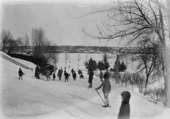 Black and white photograph of a winter landscape with a river in the background. People of all ages mingle, with some playing hockey, and others going up and down a hill with sleds.