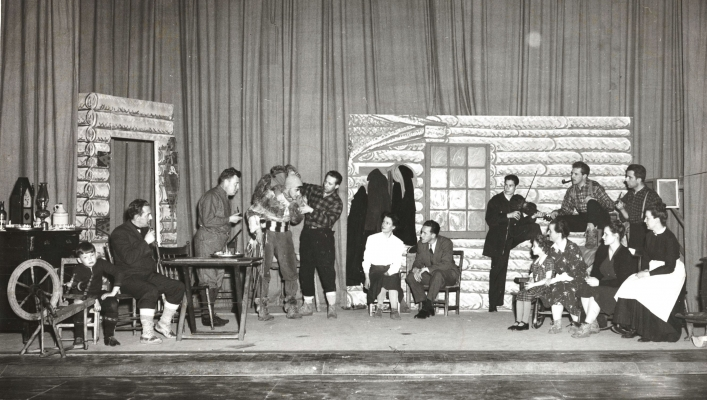 Black and white photograph of a scene from a play. About fifteen actors, men and women, dressed as early French settler and travellers. The set is the inside of a log house.
