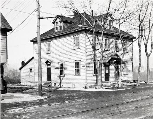 Black and white photograph of a two-storey wooden house, viewed from the side. Two dormers are set into the roof. Bare trees grow along the front of the house. There is snow on the ground.