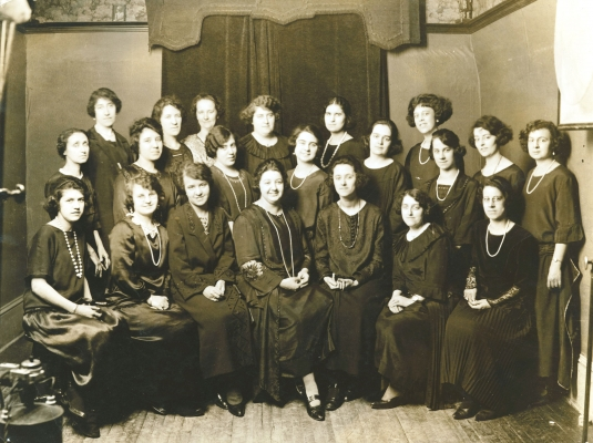 Black and white photograph depicting a group of some twenty women of various ages. Some women are seated, with others standing behind them in two rows. All wear black dresses, and many wear long pearl necklaces.