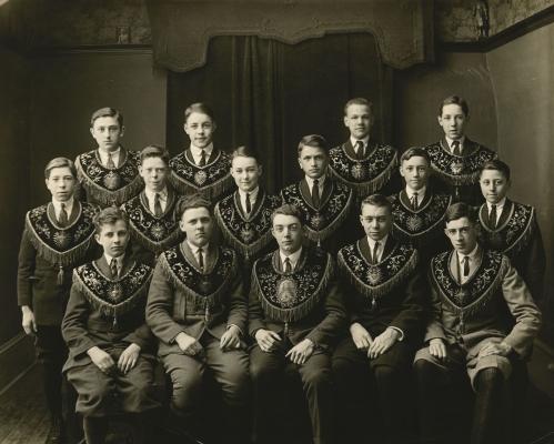 Photographie en noir et blanc d'un groupe d'une quinzaine d'adolescents. Certains sont assis, les autres sont debout derrière eux, en deux rangées. Tous portent costumes et cravates ainsi qu'une épitoge à broderie dorée et gland.