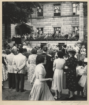 Black and white photograph of a crowd in front of a stone building with richly decorated windows. The group includes men, women, nuns and children.