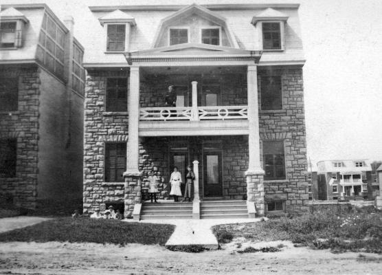 Black and white photograph of women and children in front of two adjoining three-storey stone houses with balconies.