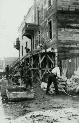 Monochrome sepia photograph of six men building a wooden, three-storey house. The site appears rudimentary, and the workers not very concerned about safety.
