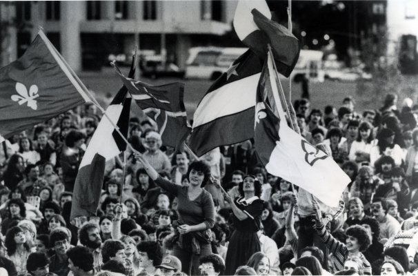 Black and white photograph of a large crowd, mostly seated. In the centre, two young women stand out from the throng, waving flags. Other people also wave flags, including two Franco-Ontarian flags and one Acadian flag.