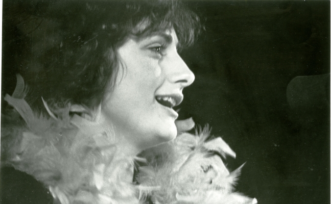 Black and white close-up photograph of a young woman in profile, singing into a microphone. She has curly, dark hair, and a feather boa around her neck.