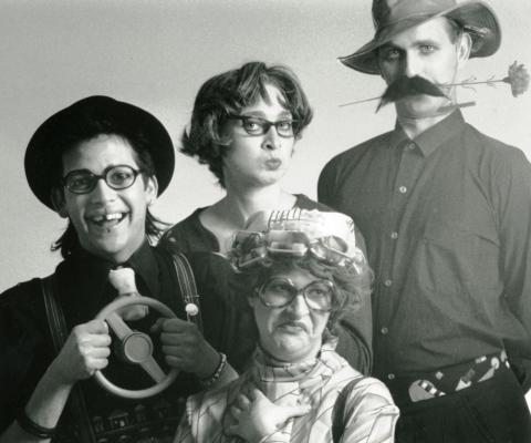 Photographie en noir et blanc de quatre comédiens costumés. Le premier porte des lunettes, un chapeau melon noir, une cravate blanche et tient un petit volant. Il lui manque une dent. Le dernier arbore une fausse moustache et un chapeau et tient une fleur dans sa bouche. Entre eux, une première comédienne porte de grosses lunettes et des bigoudis ; elle fait une grimace. La seconde porte de grosses lunettes et pince les lèvres.