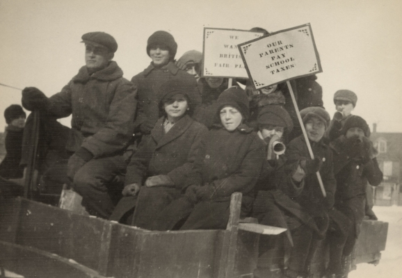 "Black and white photograph of a dozen boys dressed for winter, crowded into a cart. Two of the boys brandish placards with ""OUR PARENTS PAY SCHOOLS TAXES"" and ""WE WANT BRITISH FAIR PLAY."" Others play small musical instruments."