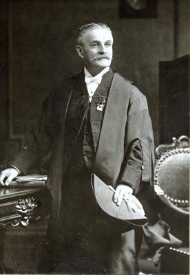 Photographie en noir et blanc d'un homme d'un certain âge, debout dans un bureau au riche mobilier. L'homme revêt la tenue parlementaire d'apparat du président du Sénat ainsi que des médailles militaires.