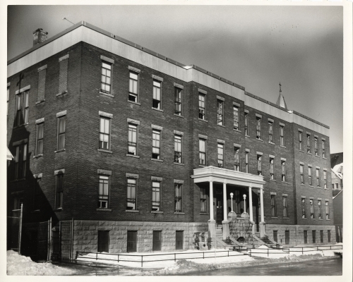Black and white photograph of a three-storey brick building with many windows. Two separate staircases lead to the main entrance.