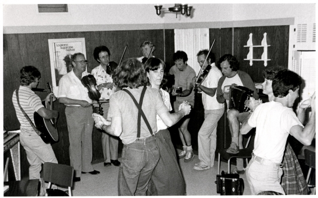 Black and white photograph of a dance party. Two young adult couples dance in the center of a semicircle formed by four fiddlers, two guitarists and an accordionist. The musicians are all men.