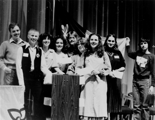 Black and white photograph of a group of young people, accompanied by some adults, grouped around a lectern. A young woman holds a document, while others hold envelopes. In the back, another group member holds up a Franco-Ontarian flag.