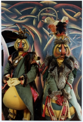 Colour photograph of two costumed characters during a theatrical performance. Masks have big orange noses, large eyes, long eyelashes, and bulging bellies. Actros wear flashy hats as well as fur-trimmed clothing. In the background, a set painted with flowing patterns in different colours.