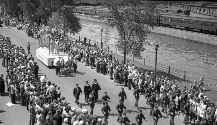 Black and white photograph of an imposing crowd watching a parade alongside a canal. Soldiers and clerics walk in front of an allegorical float pulled by horses. A train passes on the opposite bank.