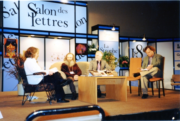 "Colour photograph of a group of three men and a woman, on a stage. The first man stands out with his long red beard. They sit around a coffee table with a book display. Behind them, a decor composed of sections with different words, including ""Salon des lettres."""
