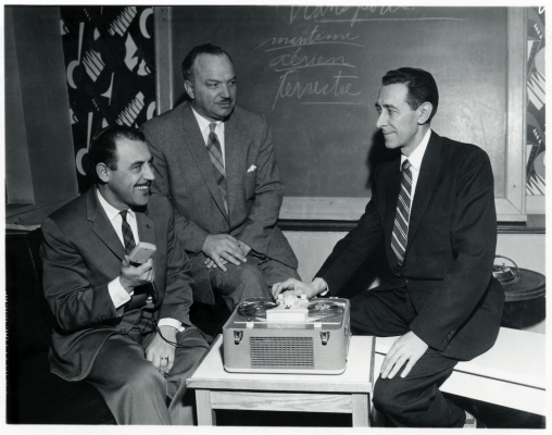 Black and white photograph of three mature men in suits and ties. One of them has a big smile. They sit around a tape recorder on a table, with a chalkboard behind them.