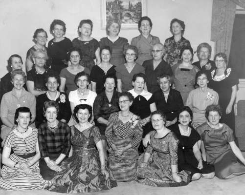 Black and white photograph, taken in a living room, of some thirty adult women. They are positioned in four rows, with the first two sitting, and the others standing. Most of the women are middle-aged. All wear elegant dresses and smile at the camera.