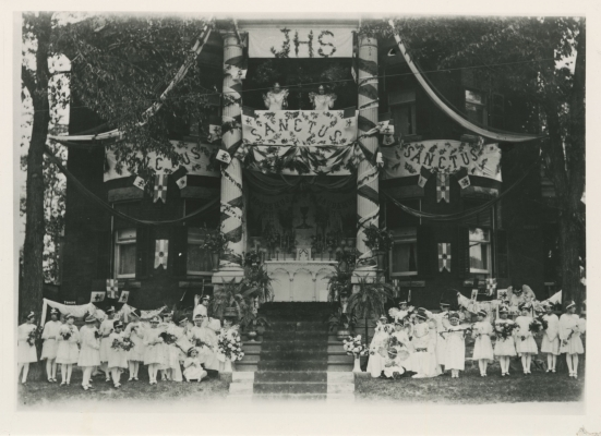 Black and white photograph of an altar at the front of a three-storey house, decorated with banners and streamers. About thirty children – dressed in white, wearing crowns and wings, holding bouquets of flowers – stand or sit on either side of the stairway leading to the altar.